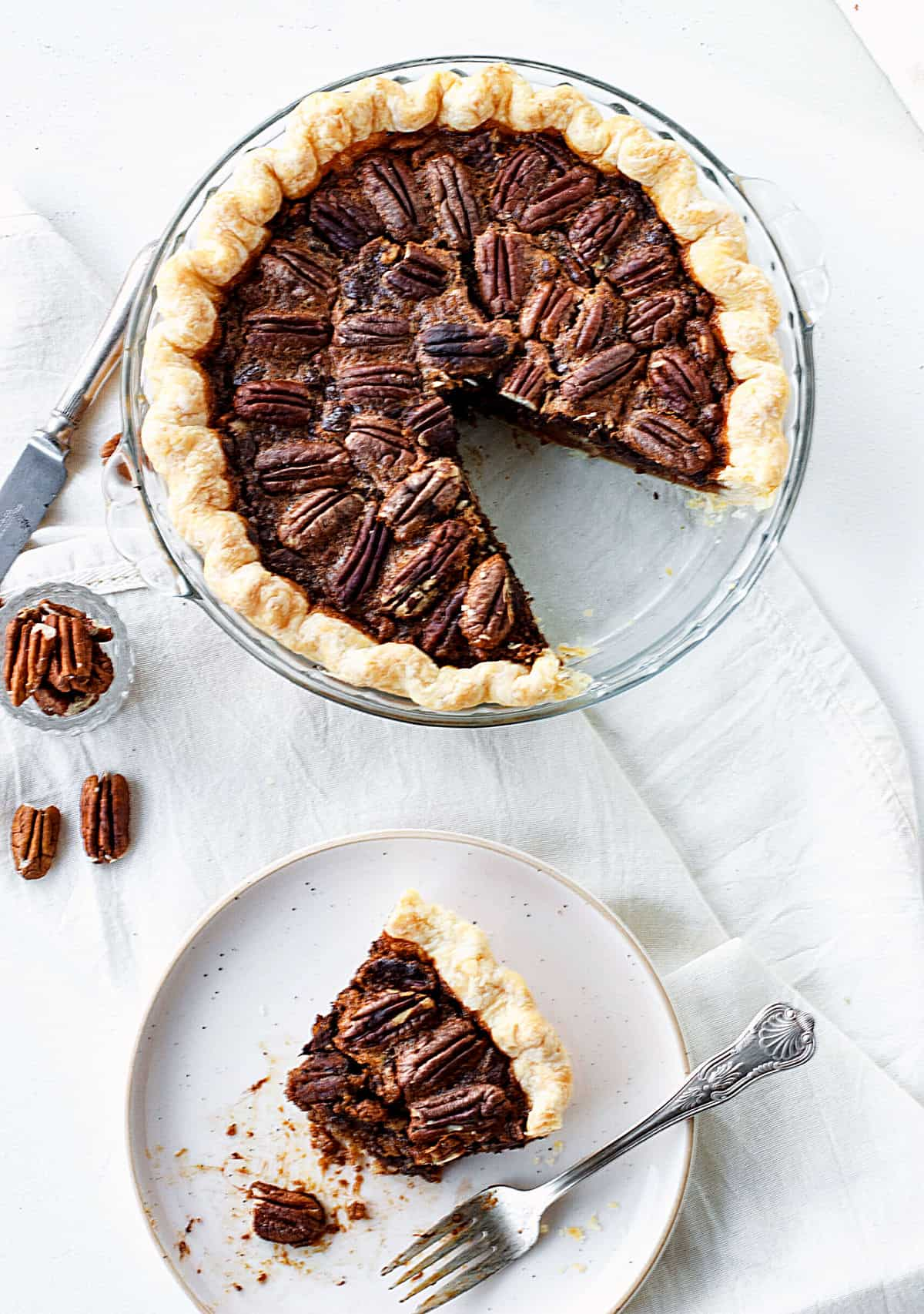 Aerial view of pecan pie in glass dish, slice on a plate with fork, white cloth and surface, loose pecans
