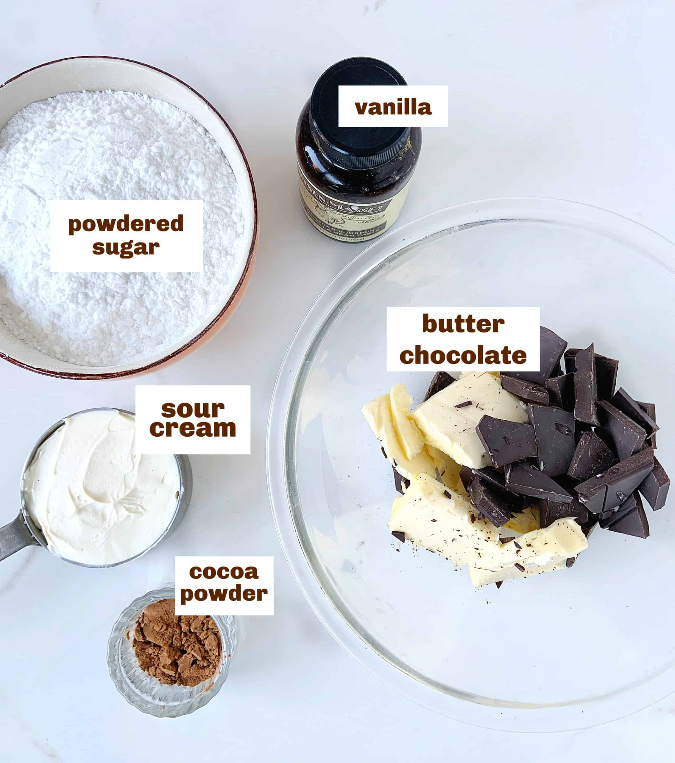 Bowls with ingredients for chocolate frosting, white surface