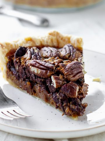 White background and plate with slice of pecan pie, a silver fork