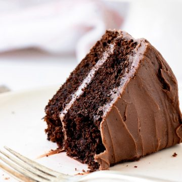 White pinkish background and plate with eaten slice of double chocolate cake, silver fork