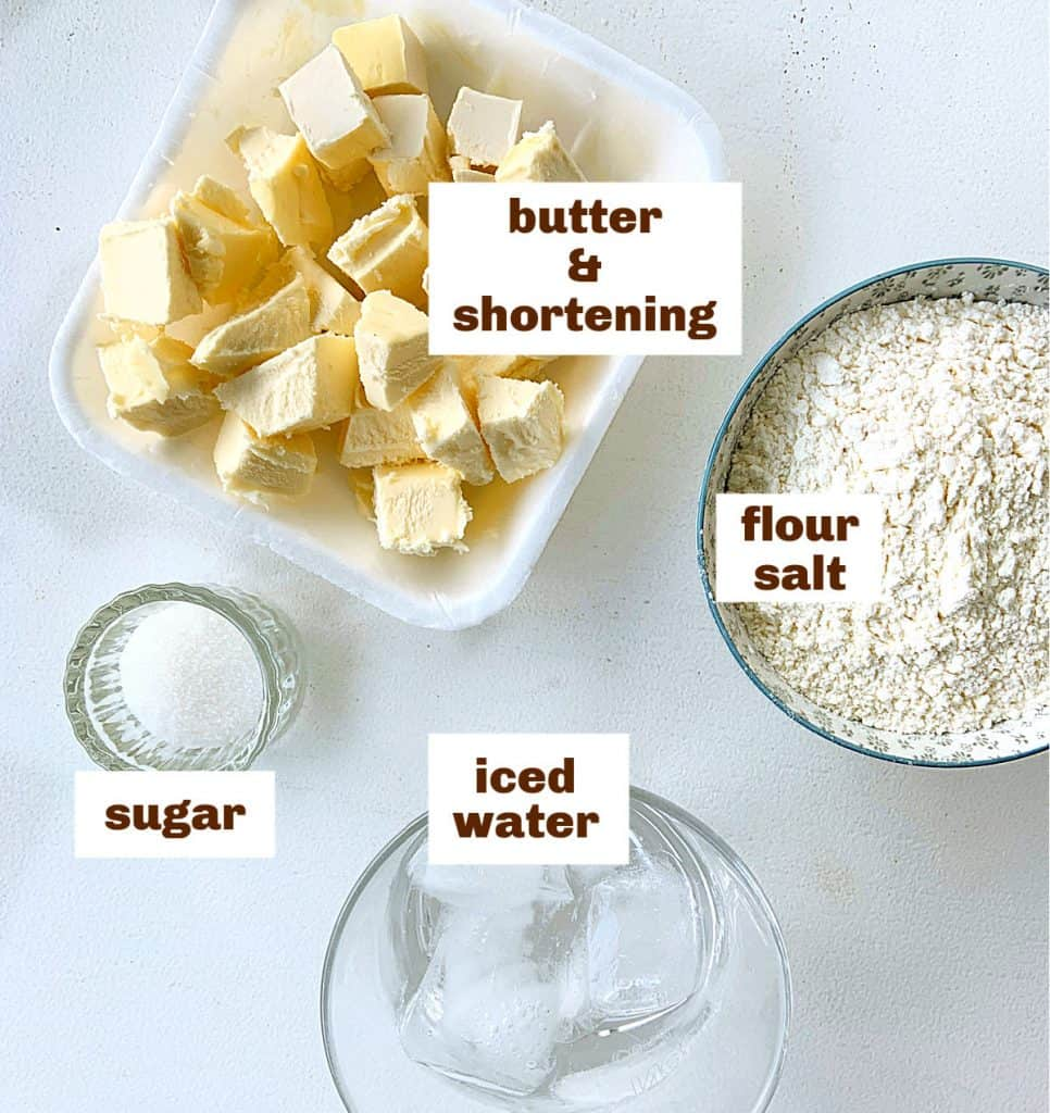 Ingredients for pie crust: butter, flour, water, sugar on a white table