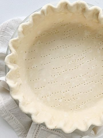 Partial view of unbaked pie crust with crimped edges on a white linen and table