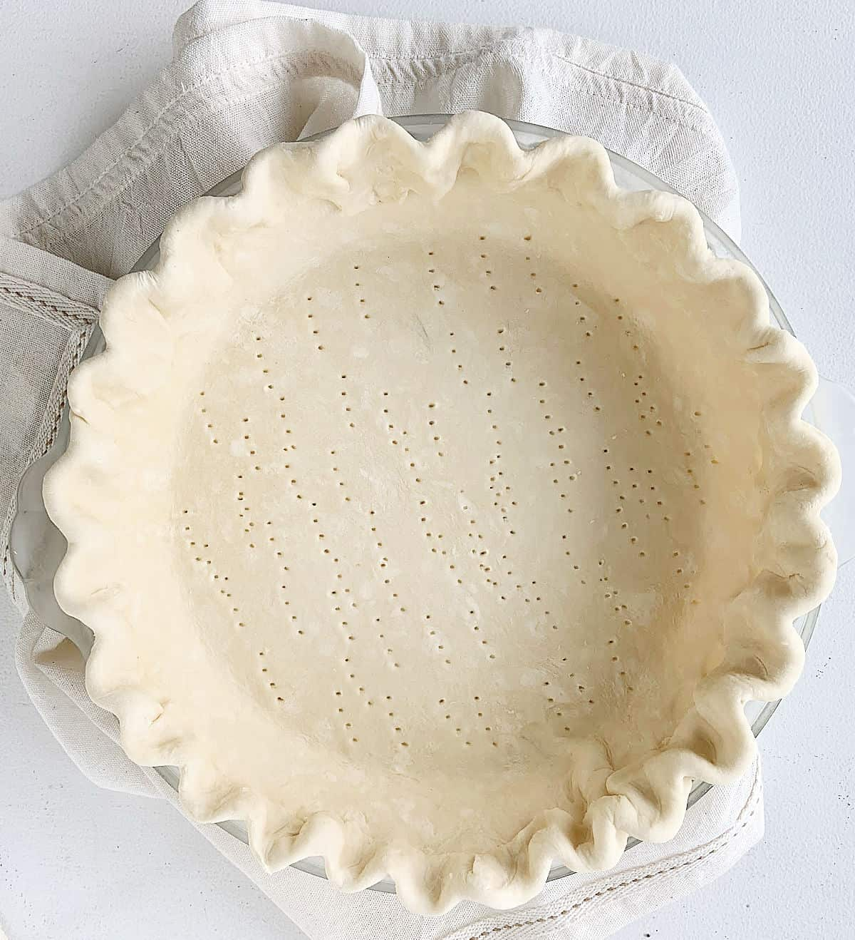 Unbaked whole pie shell with crimpled edges on a light beige cloth on a white table