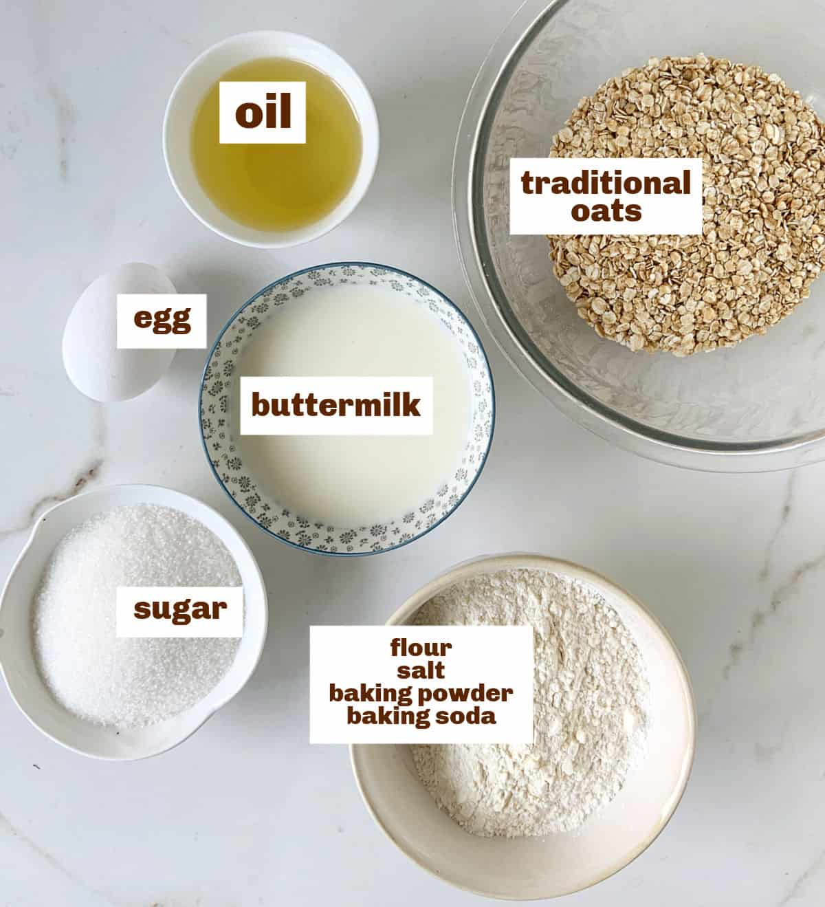 On a white marble surface several bowls with ingredients for buttermilk oatmeal muffins, including oil