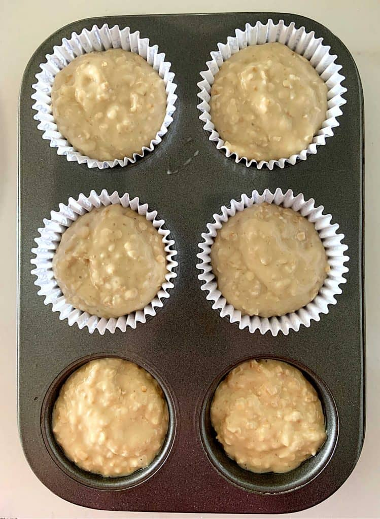 Dark 6-muffin metal pan filled with muffin batter; four have paper liners and two don't