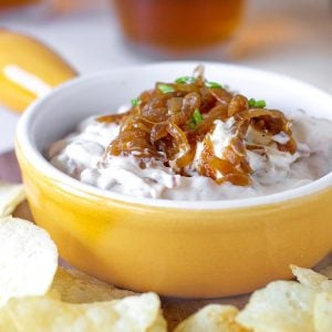 Yellow shallow dish with caramelized onion dip, potato chips around