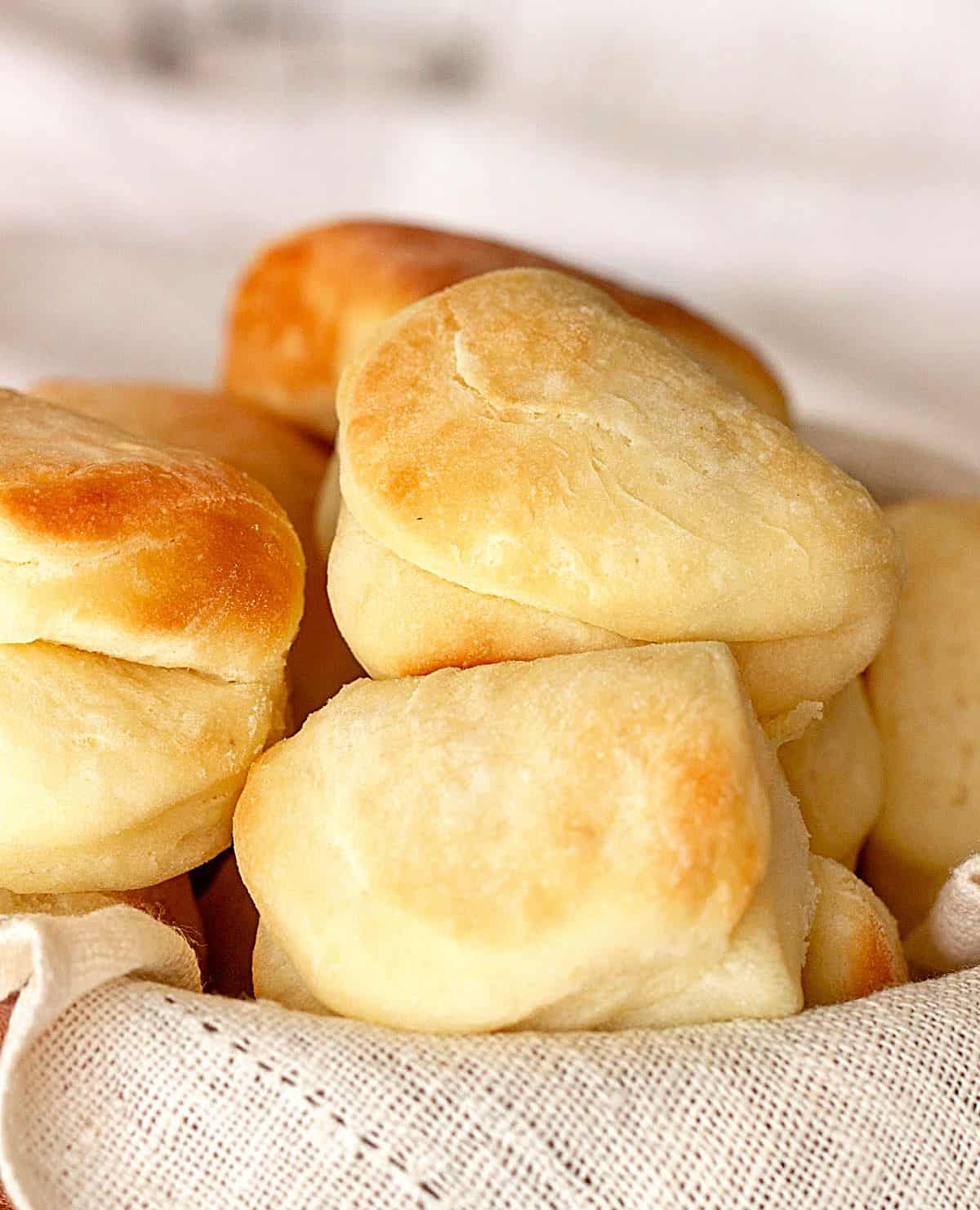A peak of linen napkin holding mound of golden bread rolls