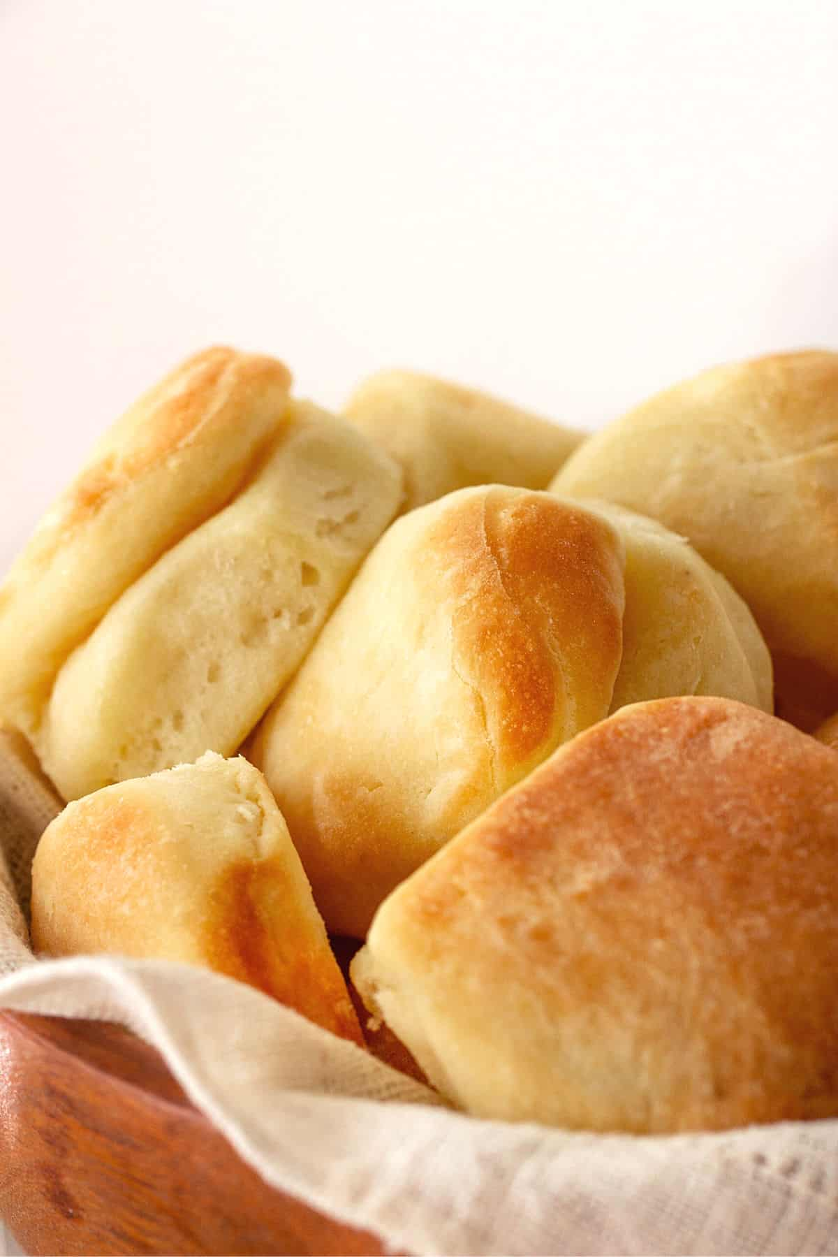 Close-up of golden parker house rolls  on a cloth in a wooden bowl