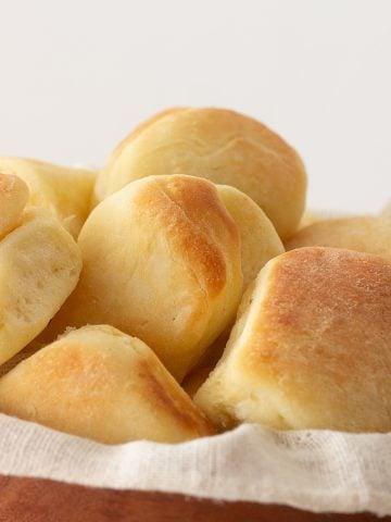 On a linen napkin several golden dinner rolls