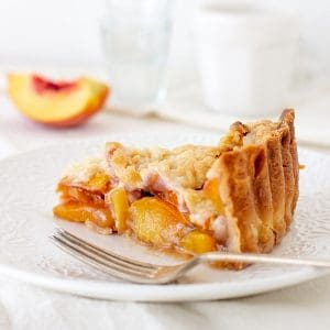Slice of peach crumb pie on white plate, white backgournd