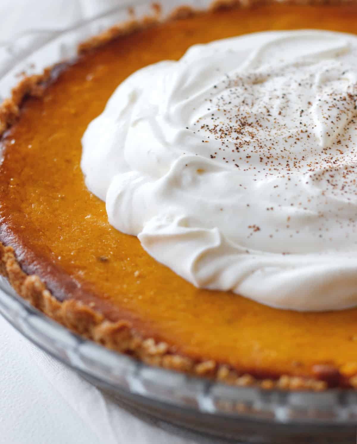 Partial view of a whole pumpkin pie topped with whipped cream