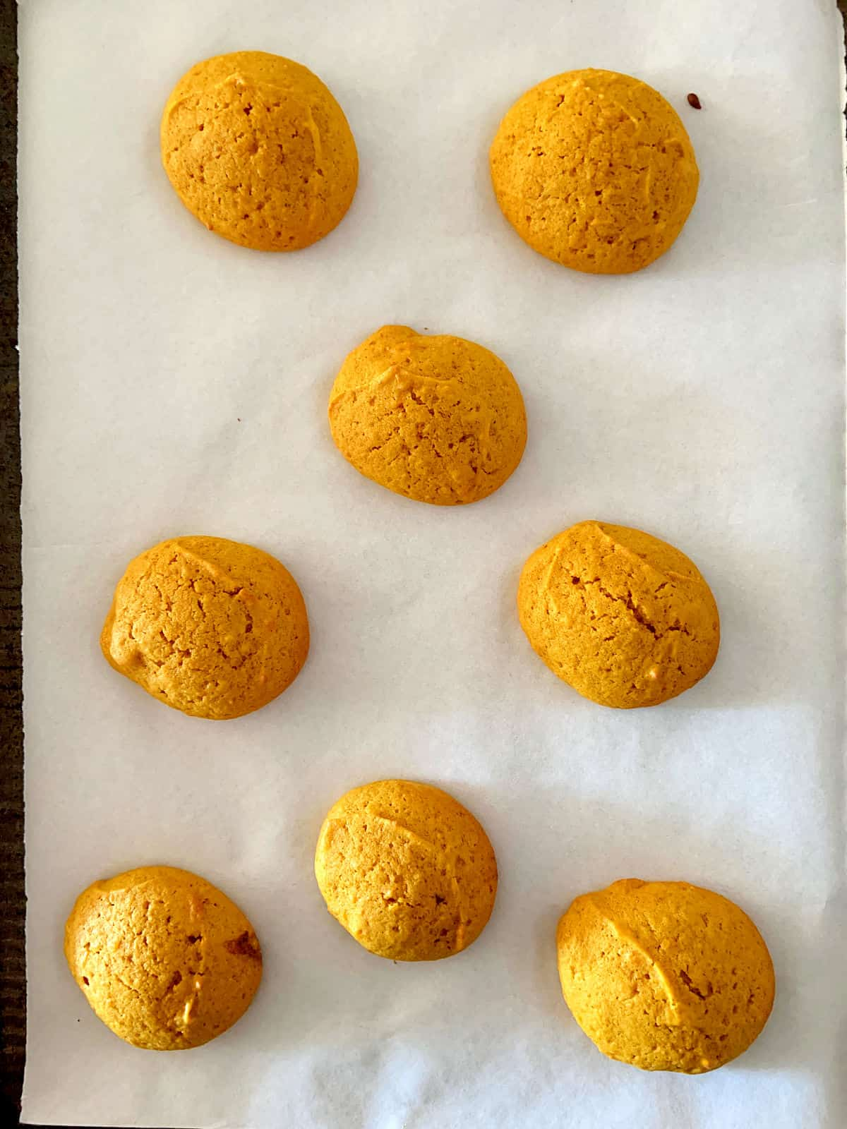 Baked pumpkin soft cookies on white parchment paper