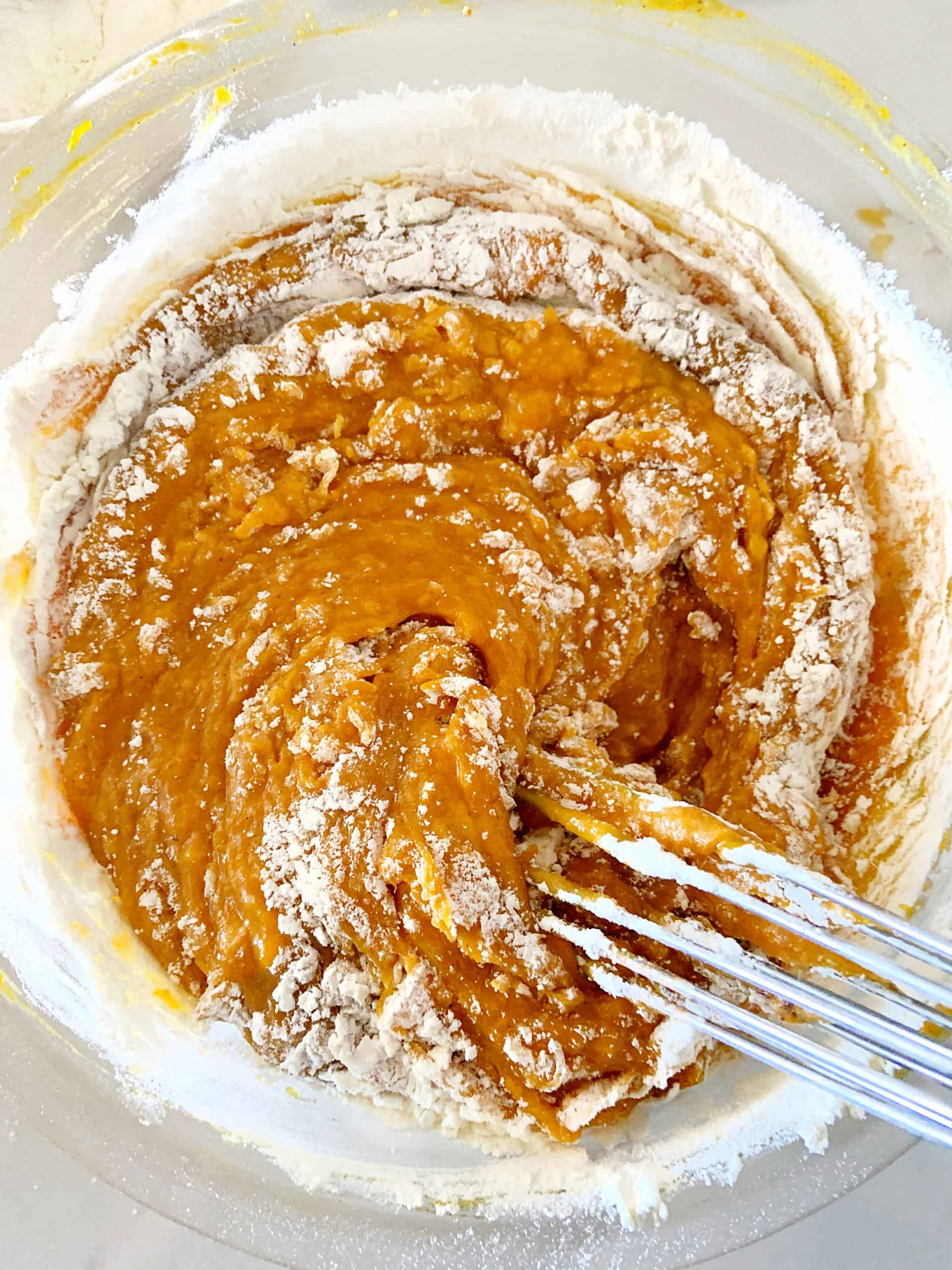 Flour added to pumpkin cake mixture, a metal whisk, glass bowl and off-white surface