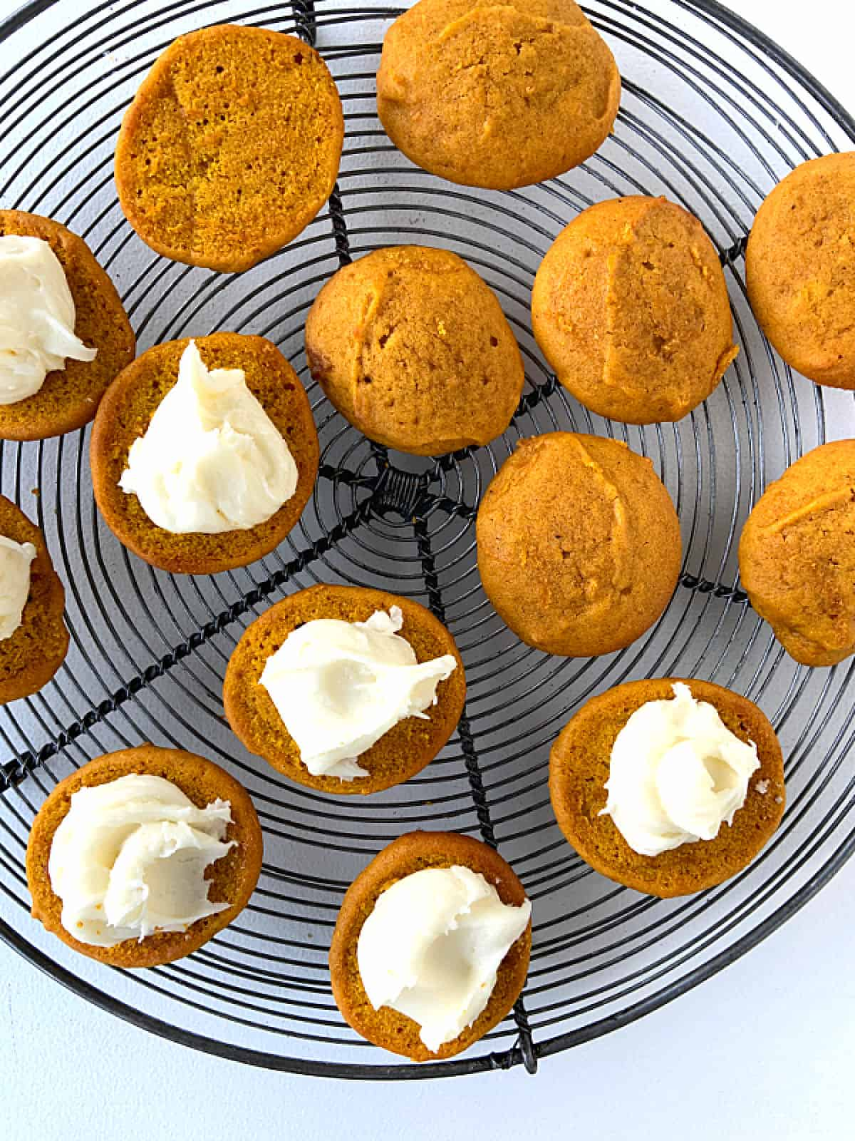 Several pumpkin whoopie pie cookies on a wire rack, some with filling, some plain