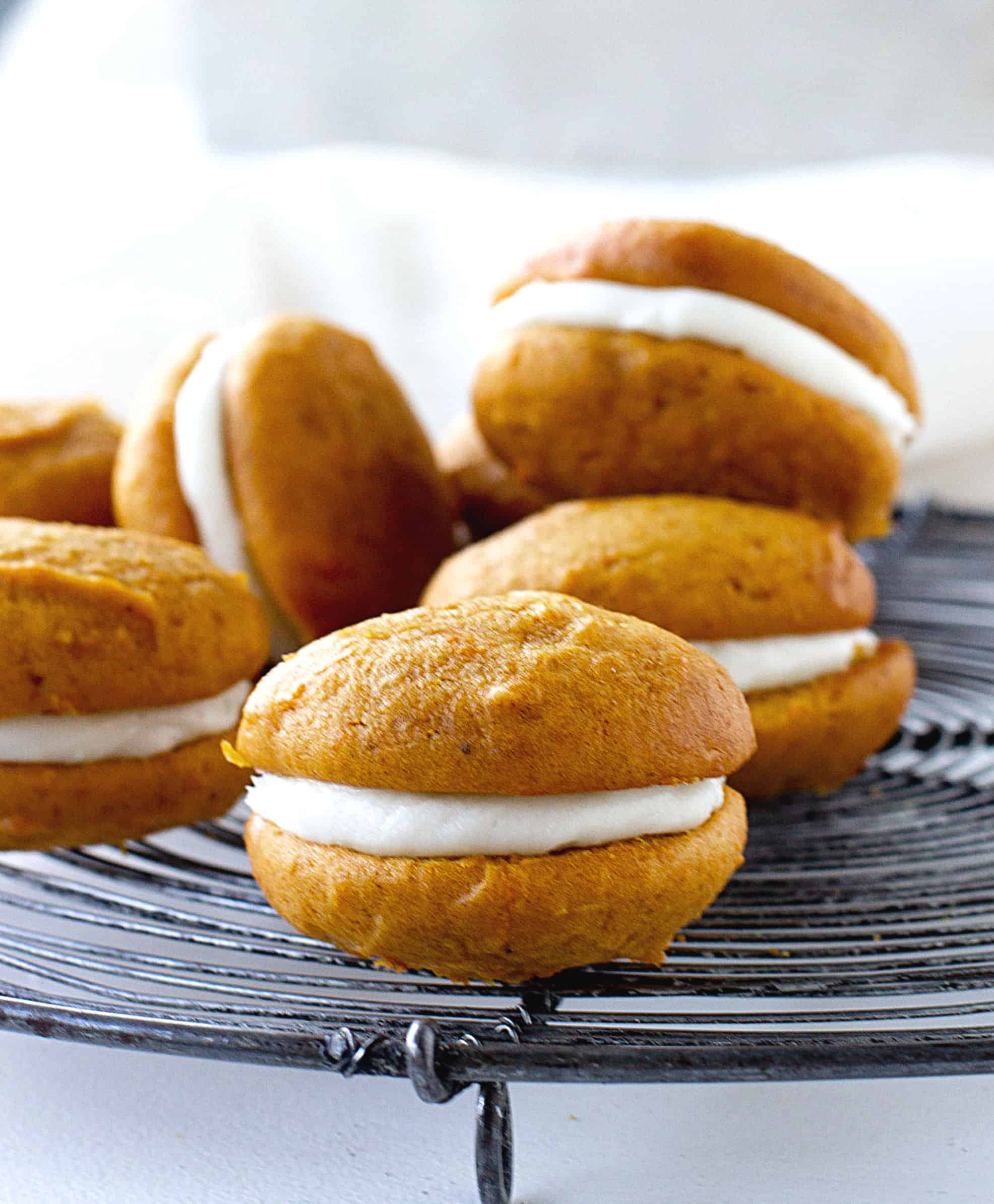 Several pumpkin whoopie pies on a dark wire rack, grey background