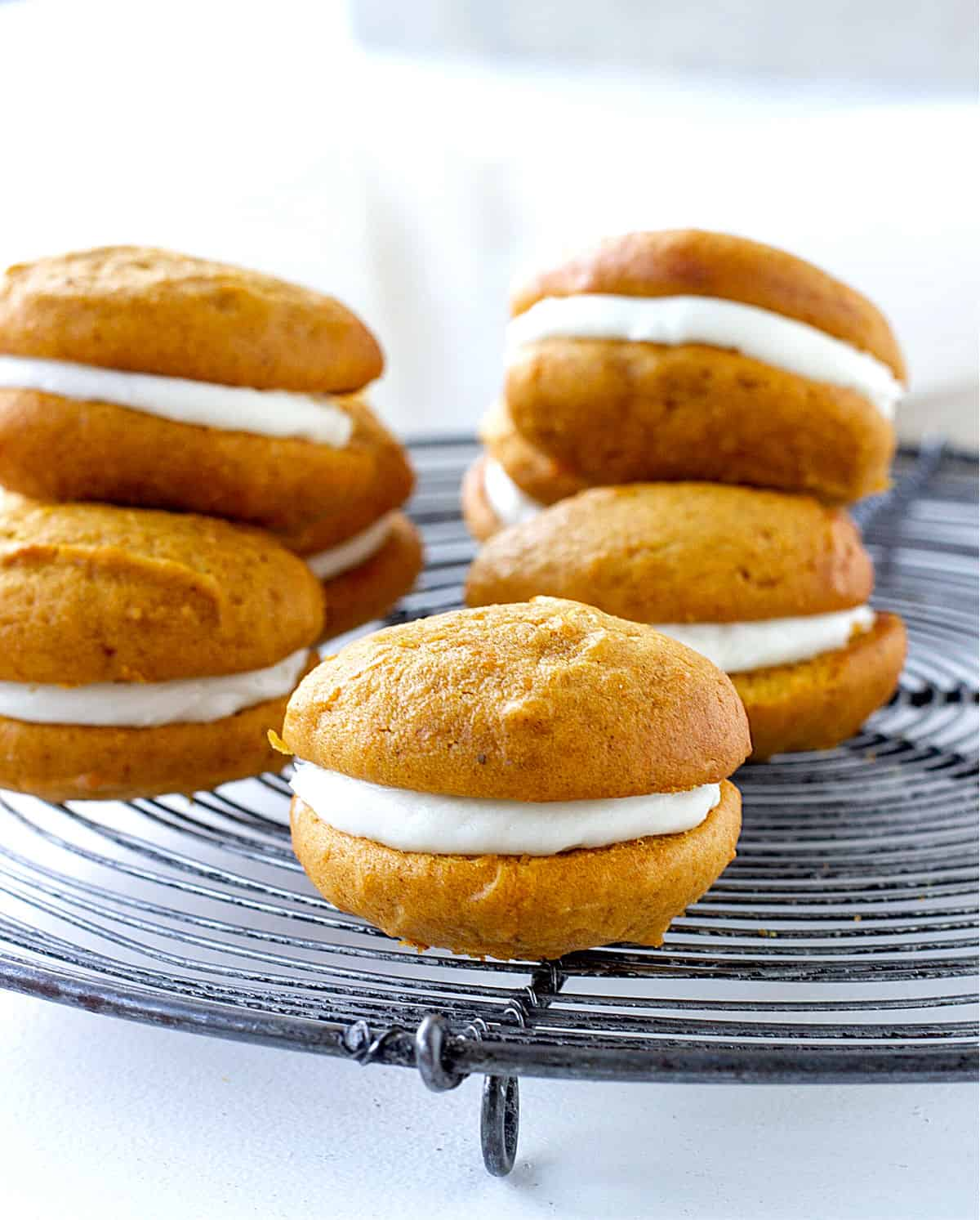 One pumpkin whoopie pie in focus and several others blurred on a round wire rack