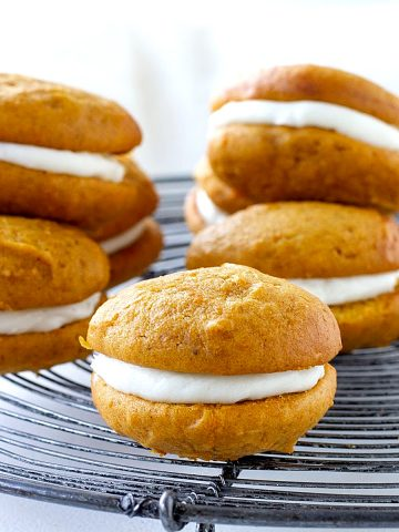 On a metal wire rack, several pumpkin whoopie pies, greyish background