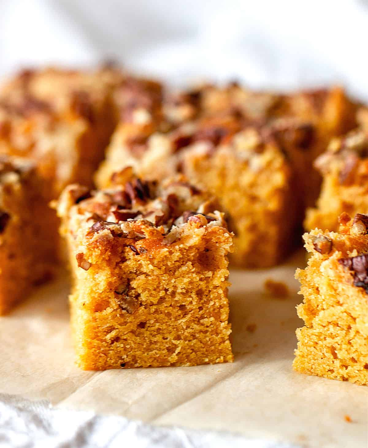 On brownish parchment paper, squares of pecan topped pumpkin sheet cake