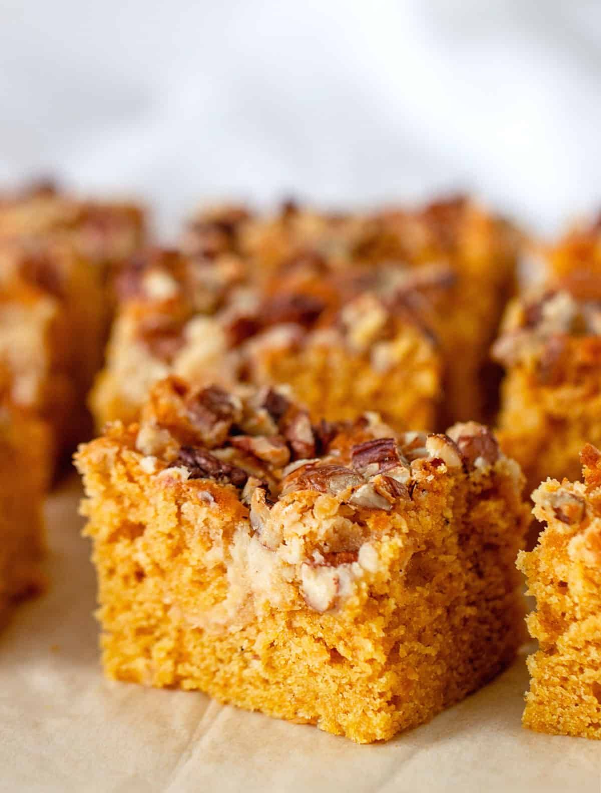 One main square of pecan topped pumpkin cake, others blurred in grey background