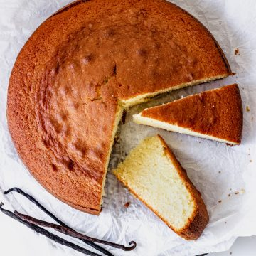 Top view of round plain vanilla cake on white paper, whole vanilla beans, two cut slices