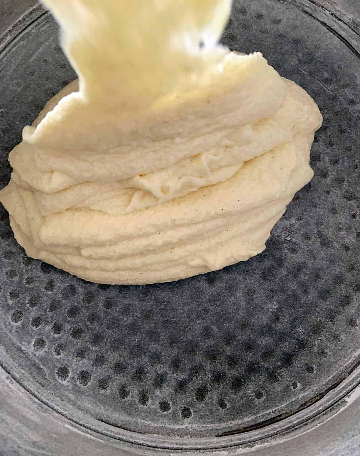 Pouring thick vanilla cake batter onto dark metal cake pan