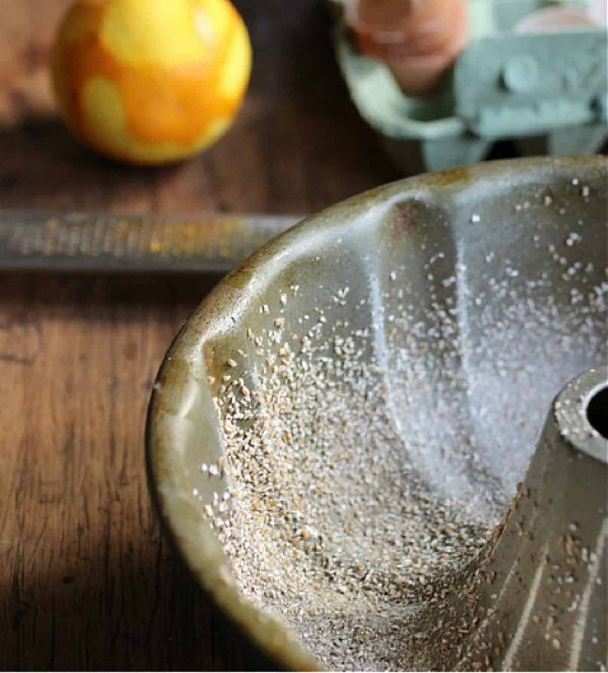 Partial view of bundt pan, an orange and egg container on wooden table