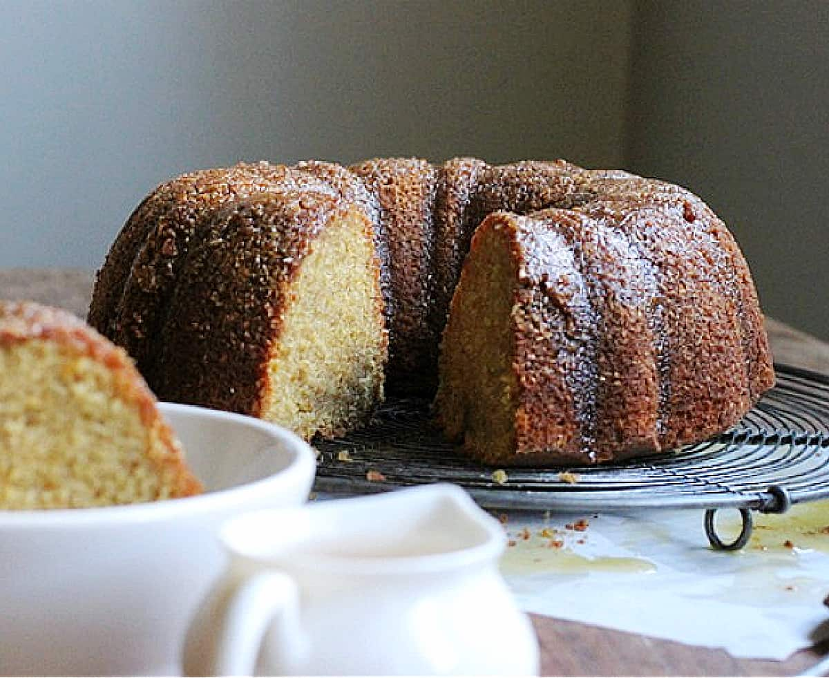 Whole bundt with slice missing on wire rack, white bowl and saucer