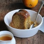 Square sized image of white bowl with bundt cake, caramel sauce, silver spoon, on a wooden table