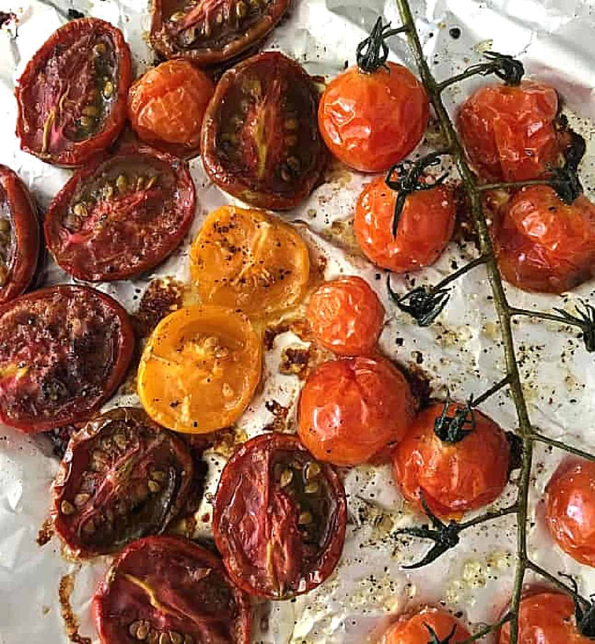 Baked tomatoes, halved and whole, on piece of aluminum paper