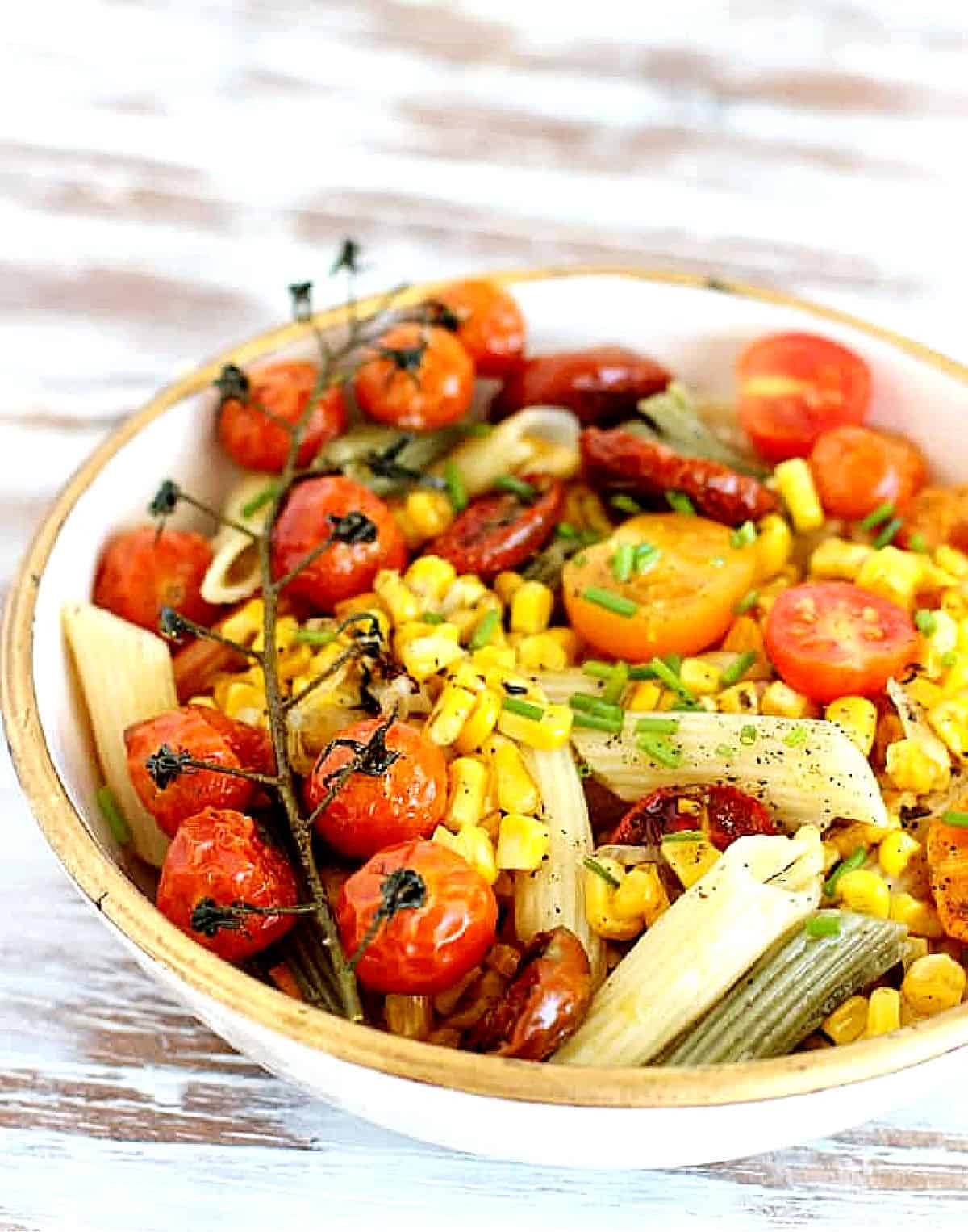 Close up of pasta cream and gold bowl with corn and tomatoes