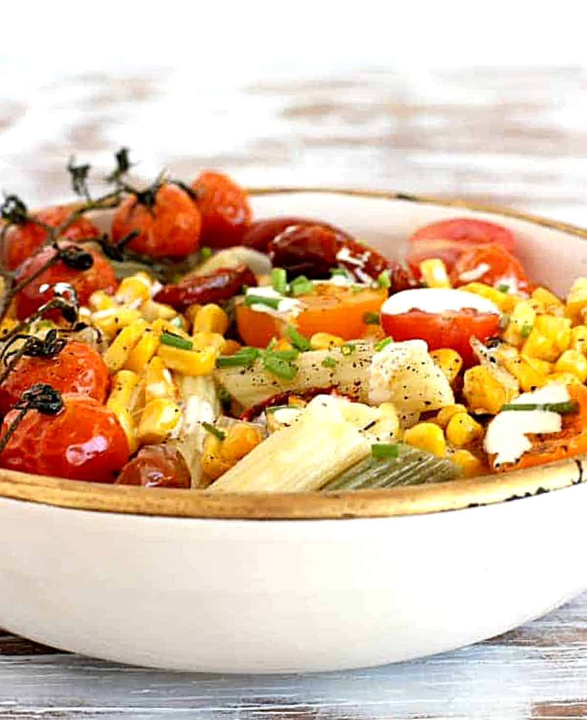 Front view of pasta plate with gold rim, mound of penne, tomatoes, corn