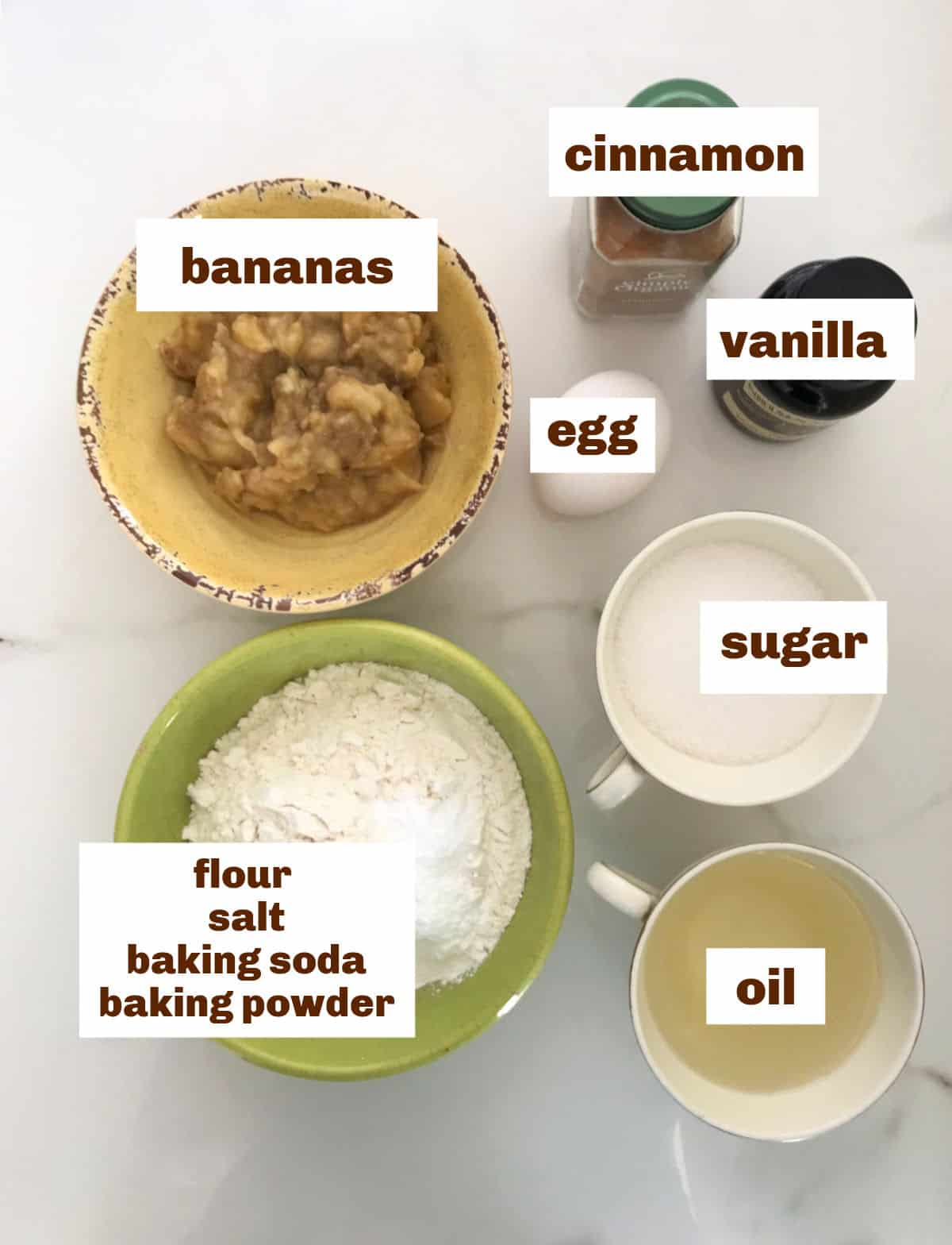 Bowls with ingredients for banana cake on a white surface