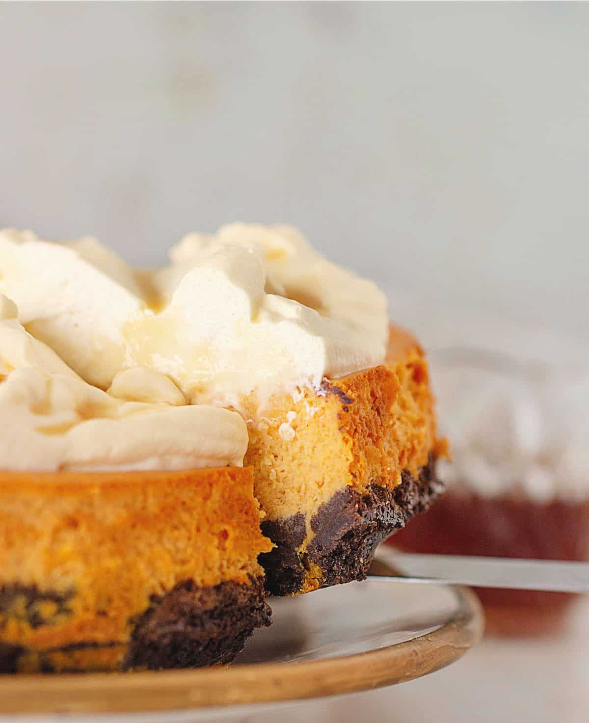 Removing slice from plate with creamy pumpkin cheesecake