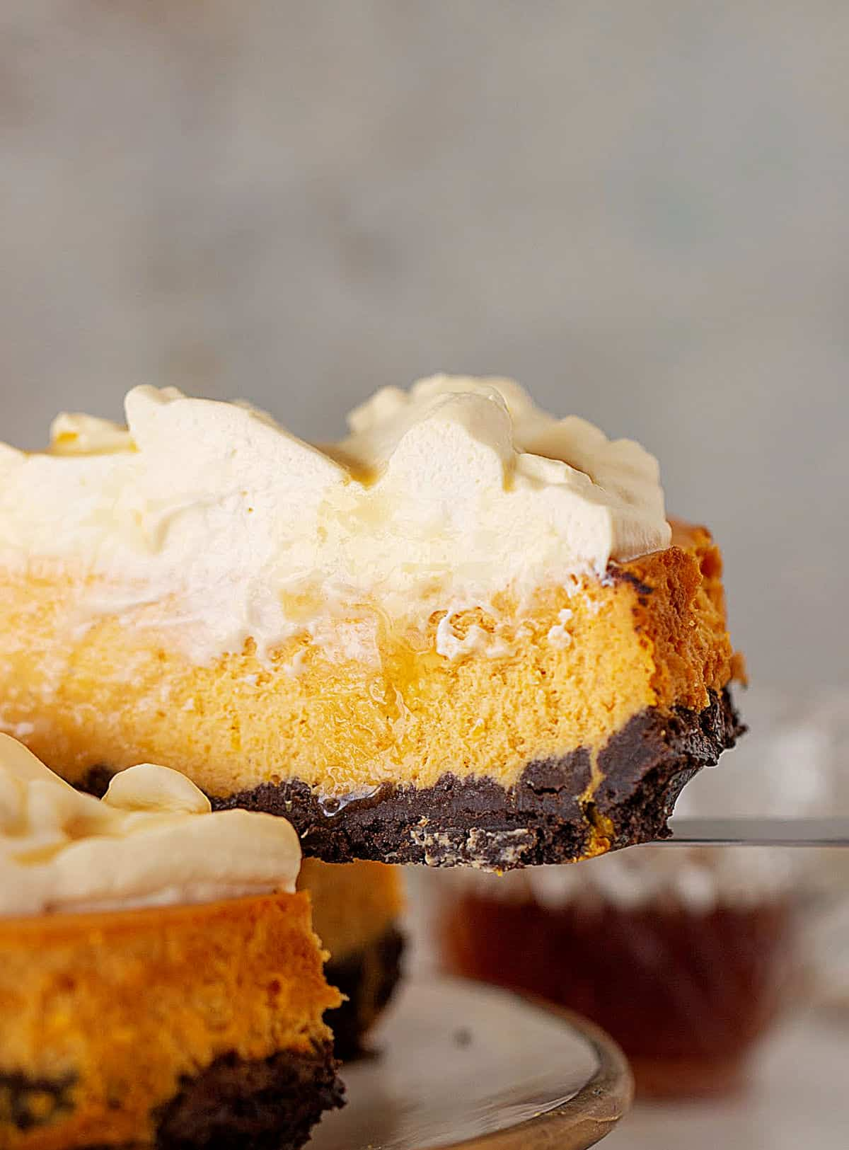 Partial slice of pumpkin cheesecake with whipped cream and chocolate crust, grey background