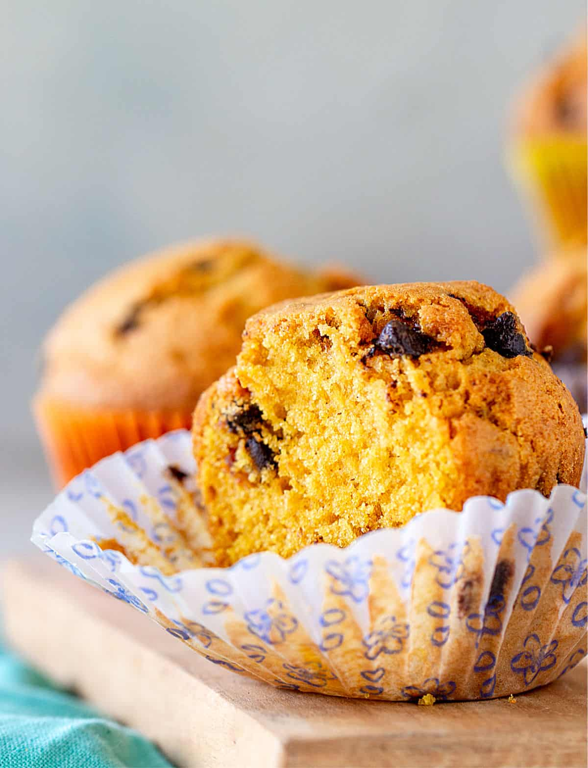 Half pumpkin muffin in opened paper liner on a wooden board