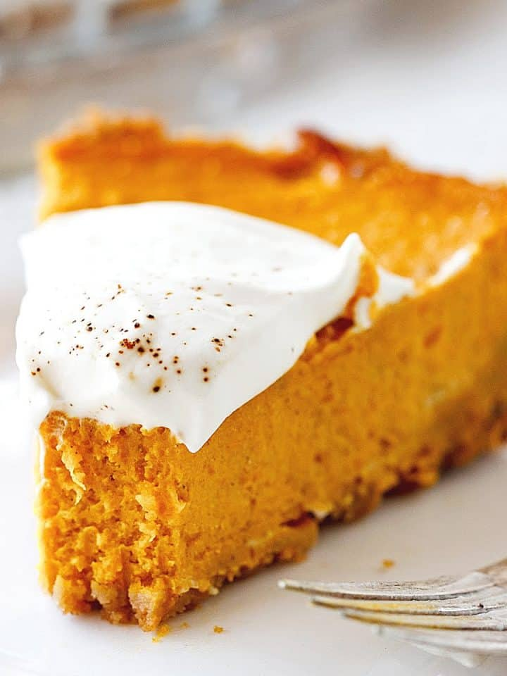 Pumpkin pie slice, bitten, topped with whipped cream, on a white plate