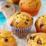 Pumpkin muffins with chocolate chips on wooden board in colored paper liners