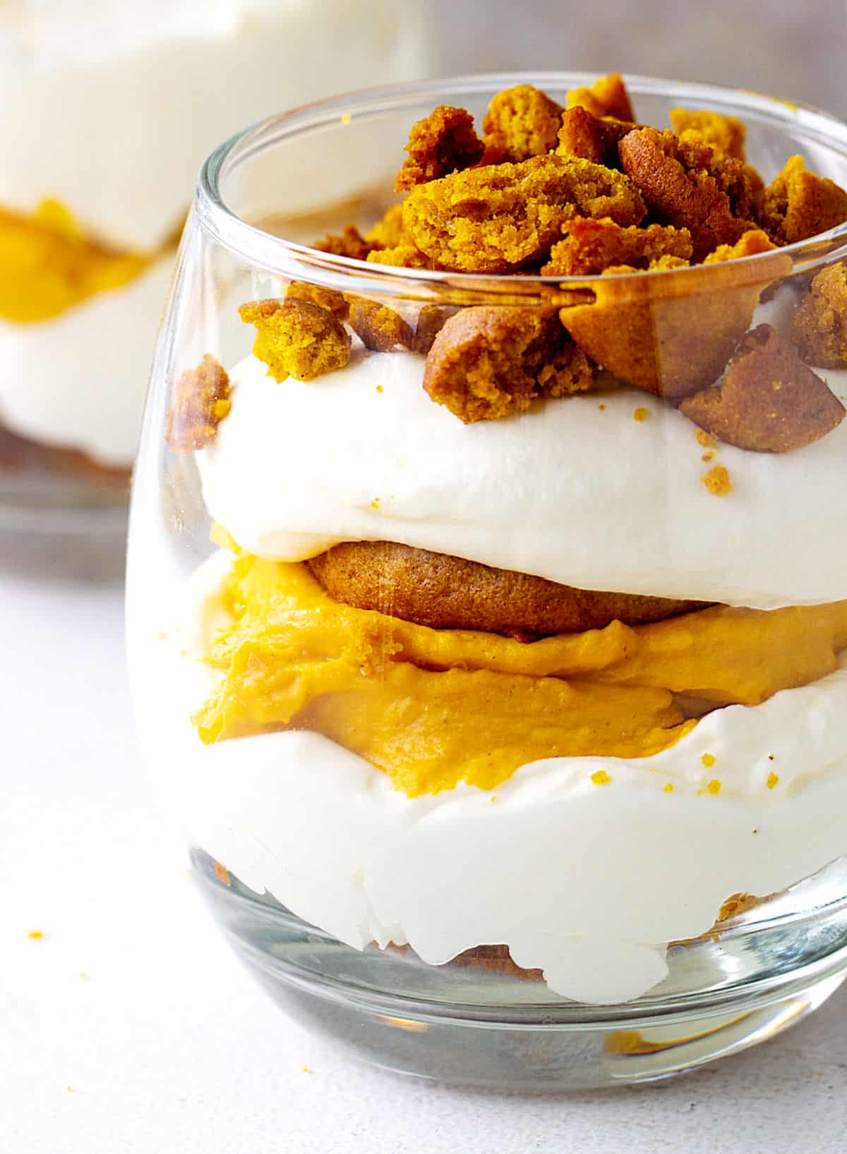 Close-up of glass with pumpkin cake, whipped cream, and pumpkin cheesecake; white surface