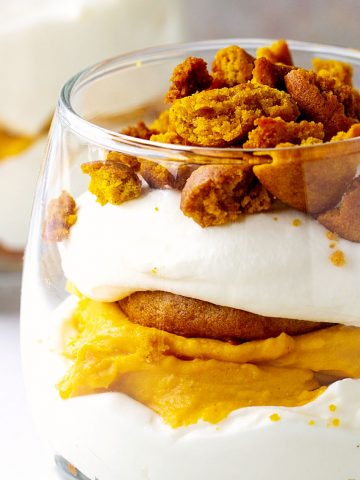 Partial close-up view of pumpkin trifle with whipped cream in a glass