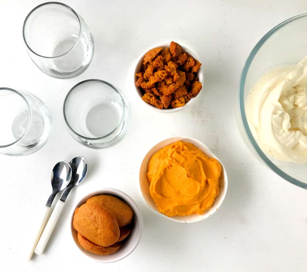Overview of glasses, bowls with pumpkin mixtures, spoons, all on a white surface