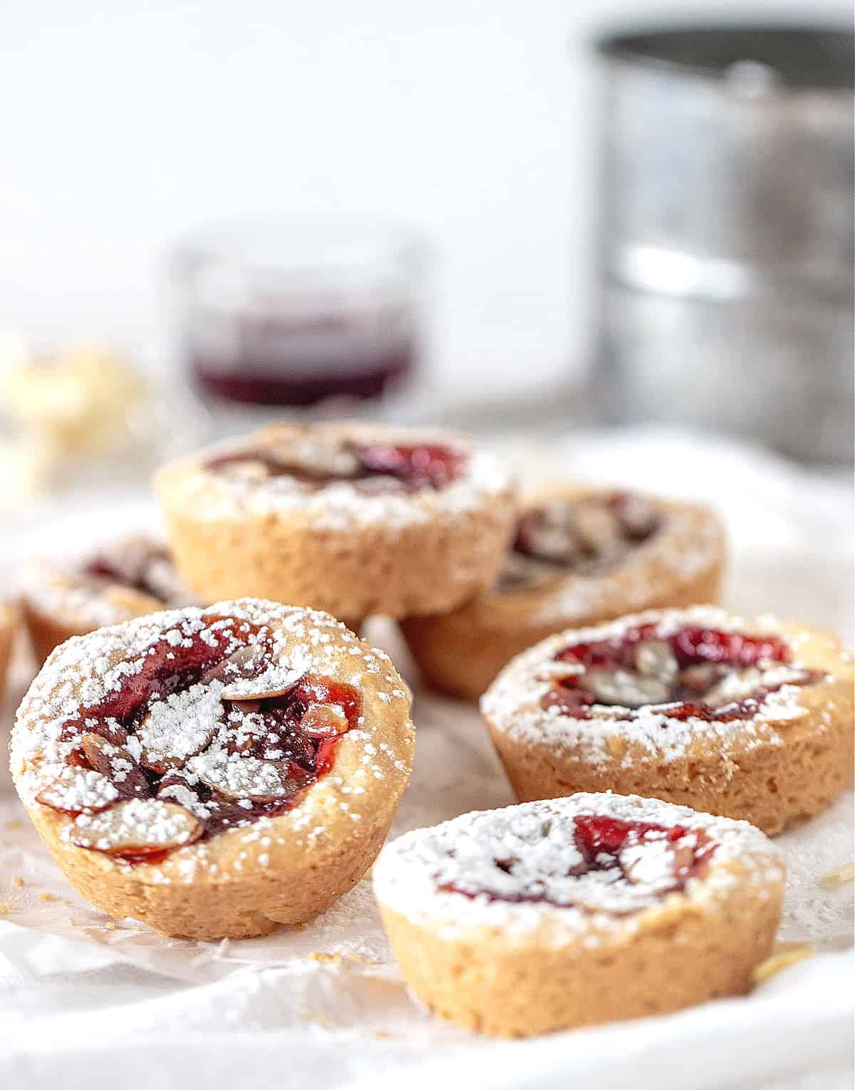 Jam tarts on top of a white cloth, a metal sifter and glass in background