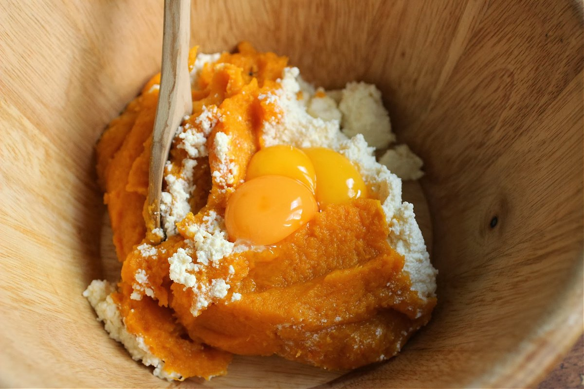 Wooden bowl with pumpkin puree, ricotta and egg yolks; a wooden spoon inside
