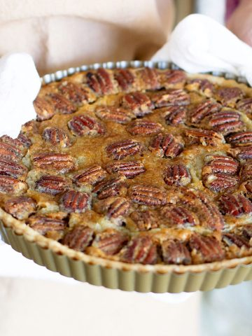 Hands holding whole pecan pie in the pan with white kitchen towel
