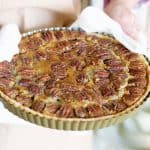 Holding tart pan with baked pecan pie and a white kitchen towel