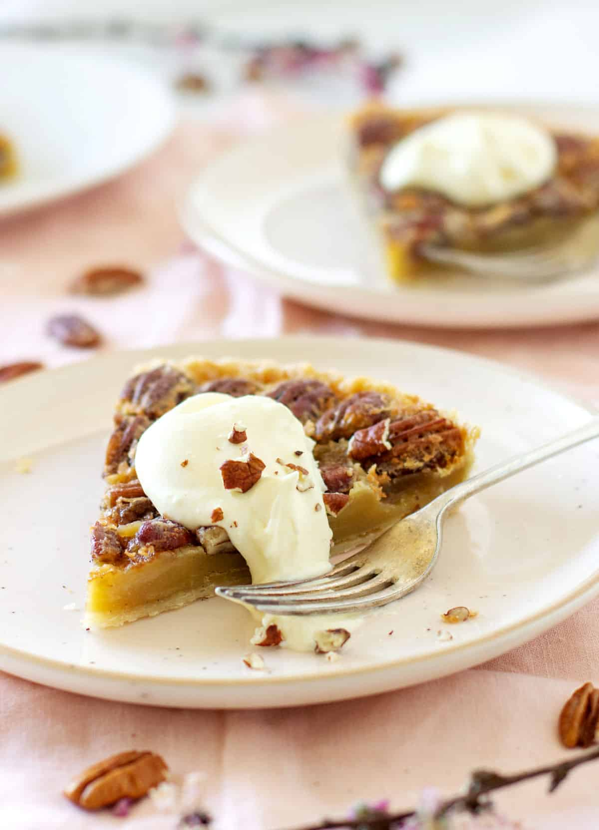 Slices of pecan pie with whipped cream on pink plates and embroidered tablecloth