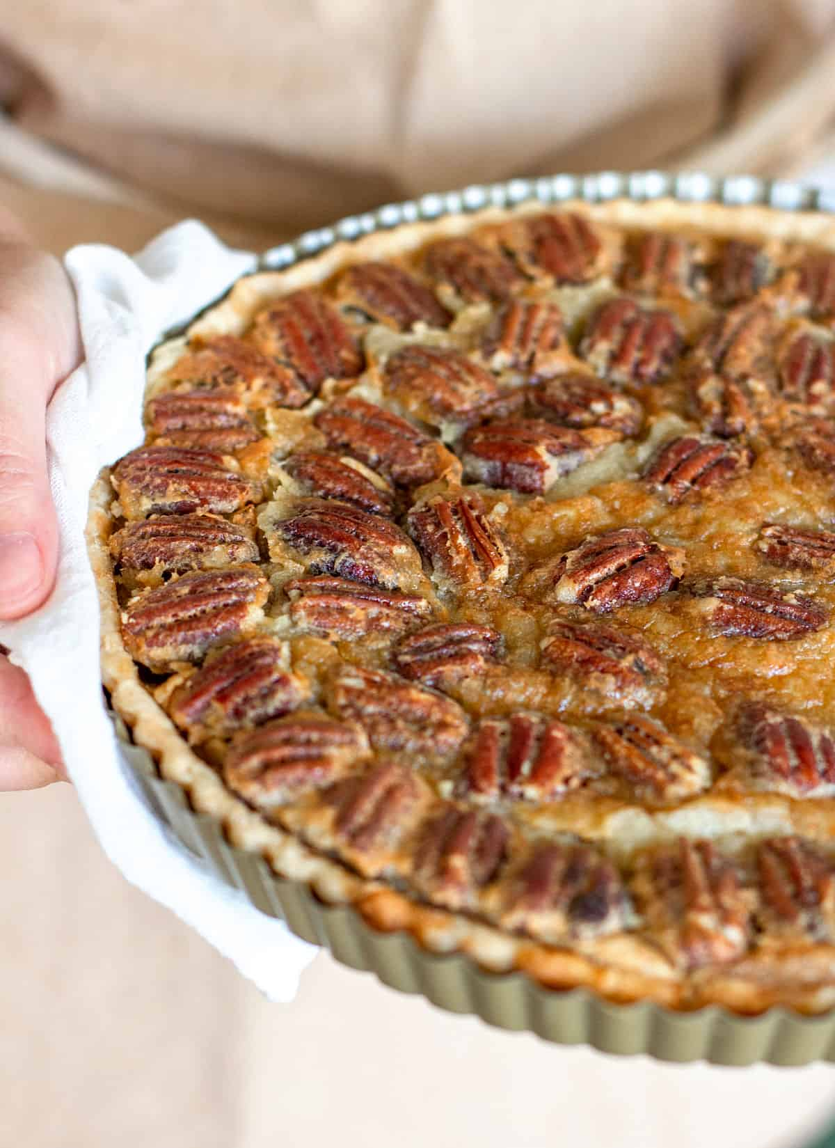 Partial view of hands holding pecan pie with white kitchen towel, beige apron