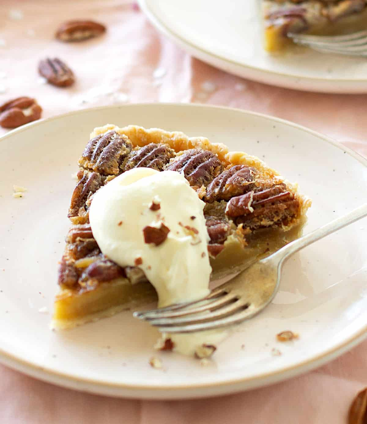 Single slice of pecan pie in light pink plate, dollop of cream, fork. Pink tablecloth