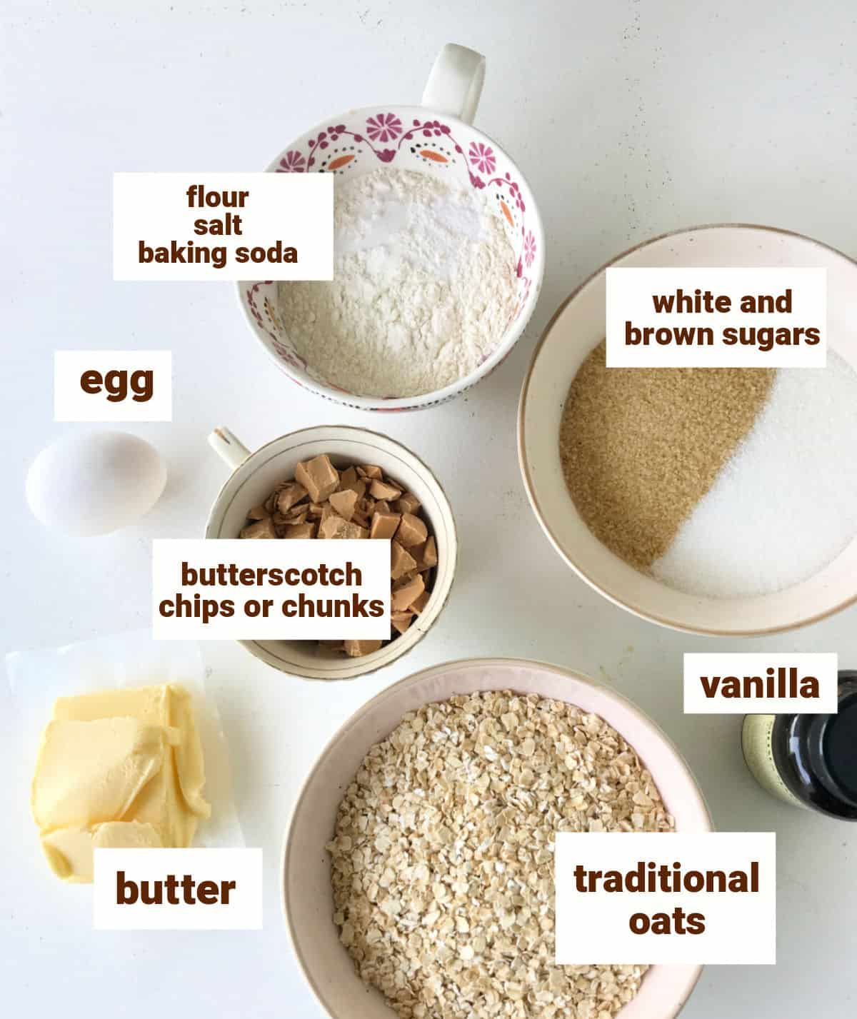 Different bowls with ingredients for oatmeal butterscotch chip cookies on white surface