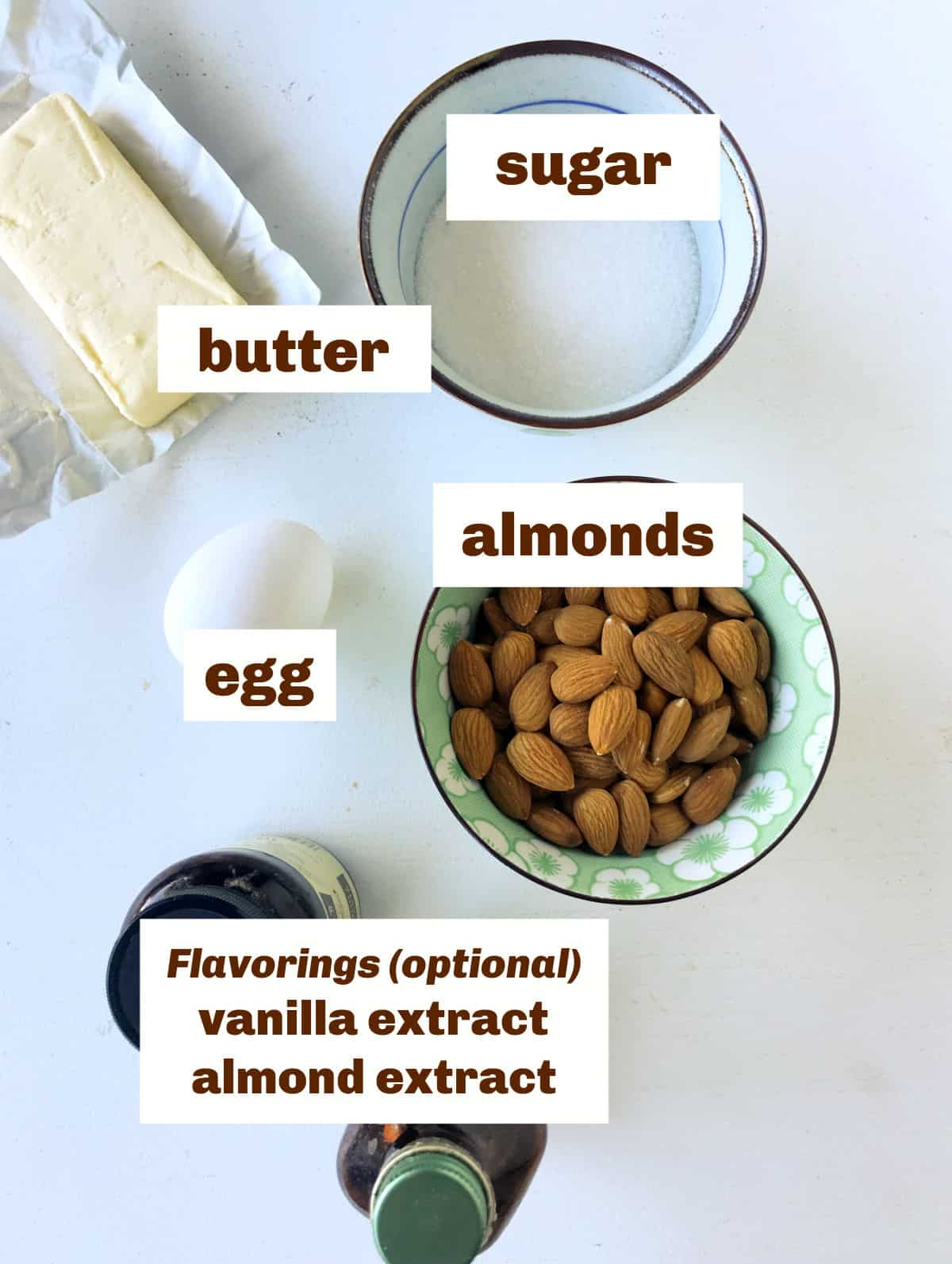 Whitish surface with almond cream ingredients including butter, almonds, and sugar in bowls