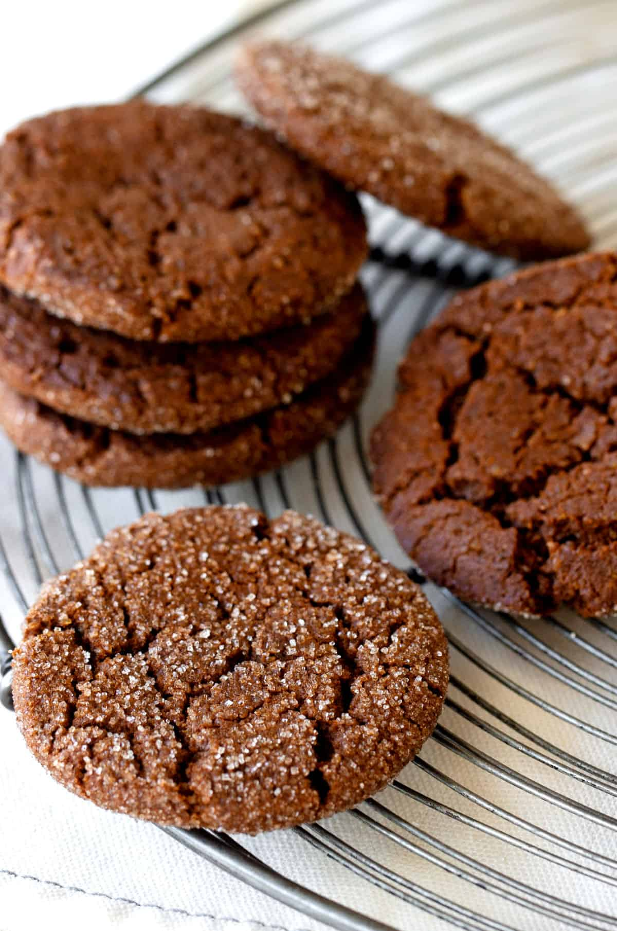 Several dark molasses cookies, stacked, on wire rack